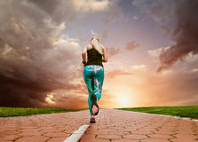 Young blonde girl evening jogging with great cloudscape Stock Photography