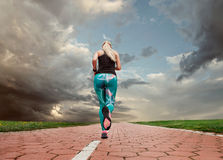Young blonde girl evening jogging with great cloudscape Stock Images