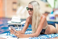Young blonde girl freelancer in bikini works near the swimming p. Ool, in social media with mobile smart phone, getting sun tan stock photography