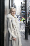 Young blonde girl in a fur coat posing near Oxford Street. Stree Royalty Free Stock Image