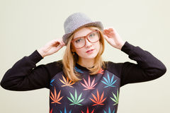 Young blonde girl in glasses touching her hat with Stock Image