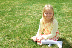 Young blonde girl on grass. Young blonde girl in pretty spring dress on the grass Royalty Free Stock Photo