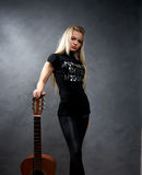 Young blonde girl with a guitar Royalty Free Stock Photography