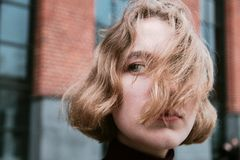 Young blonde girl with hair fluttering in the wind closeup portrait royalty free stock images