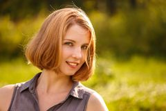 A young blonde girl happily smiling in the rays of the bright sun on green background Stock Photography