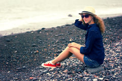Young blonde girl in a hat on the beach Stock Photography