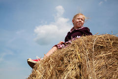 Young blonde girl in the hay under blue sky Stock Image