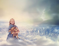 Young Blonde Girl with her Dog on Clouds Royalty Free Stock Image