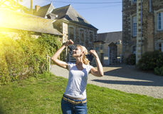 Young blonde girl holding grape in front of old French buildings in Provence Royalty Free Stock Images
