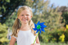 Young blonde girl holding pinwheel smiling at camera Stock Photography