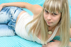 Young blonde girl in jeans and white shirt Stock Images