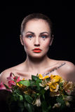 Young blonde girl keeps flowers on black background royalty free stock photography