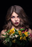 Young blonde girl keeps flowers on black background royalty free stock photos