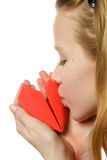 Young blonde girl kissing red heart Royalty Free Stock Images