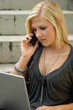 Young, blonde girl with laptop and mobile phone. Royalty Free Stock Photography