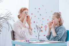 Girl learning to speak. Young blonde girl learning to speak properly with elder therapist in glasses stock photos