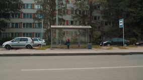 Young blonde girl in leather jacket sitting on town bus stop waiting. Young caucasian blonde girl in leather jacket sitting on town bus stop waiting, cars stock footage