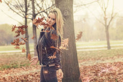 Young blonde girl levitating leaves in the autumn forest Stock Photos