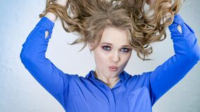 Young Blonde Girl Lifts Strands Of Hair Up And Throws Them. Hair Is Flying In Different Directions. The Face Is Hidden Royalty Free Stock Photos