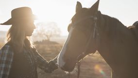 Young blonde girl with long hair in cowboy hat stroking and hugging a horse. In slow motion. Close up of beautiful young woman with her dark horse enjoying