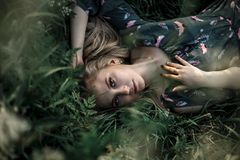 Young blonde girl with long hair lying in the grass. stock photos