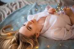 A young blonde girl in a long white male shirt lying on the bed, throwing her hair on the blanket. royalty free stock images