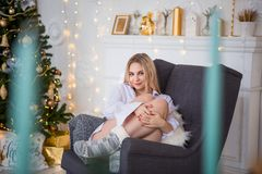Young blonde girl in a long white man`s shirt and warm socks sitting in a cozy chair. royalty free stock photos