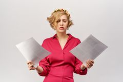 A young blonde girl with a lost view looks at the documents spreading her hands in front of her in confusion and misunderstanding. Classic red dress and a royalty free stock photo