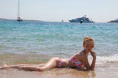 Young blonde girl lying in the sea with a white yacht background. Young blonde girl with braided hair in a bunch, with pink sunglasses, lying in the sea with stock image