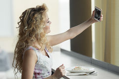 Young blonde girl making self portrait on her smart phone digital camera while sitting in cafe during lunch break.  Royalty Free Stock Photography