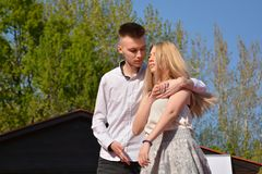Young blonde girl and the man are hugged on sunny spring day in park with green tree in background. Close up, selective focus. Lov royalty free stock photos