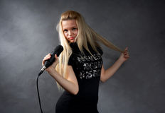 Young blonde girl with microphone Royalty Free Stock Photo