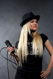 Young blonde girl with microphone Royalty Free Stock Photos