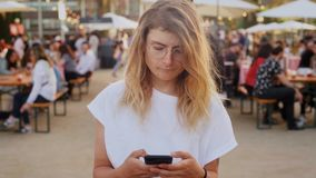 Hipster teenager at festival uses smartphone stock video footage