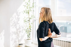 Young blonde girl near the window doing meditation. Hands in namaste behind the back Stock Images
