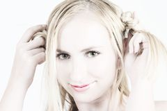 Young blonde girl playing with her hair Stock Photos