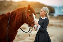 Dreamy shot of a woman with a horse near the ocean stock images