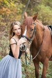 A young, blonde girl posing with a horse, a beautiful girl and a strong horse. Royalty Free Stock Photography