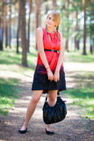 Blonde girl posing. Portrait of a young girl standing on the road in the park Stock Photos