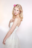 Young blonde girl posing in studio in white dress Stock Photo