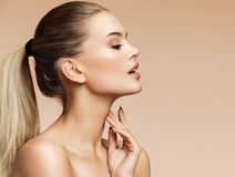 Young blonde girl in profile touching her clean skin. Royalty Free Stock Images