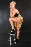 Young blonde girl puts leg on chair Stock Photos