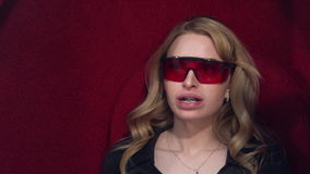 Young blonde girl puts on protective glasses getting UV whitening. Before the procedure of teeth whitening. stock video