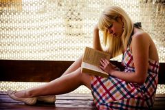 Young blonde girl reading stock image