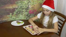 Young blonde girl in red hat sitting by the table at home kitchen. The girl is preparing for Christmas and shifts the stock video footage