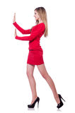 Young blonde girl in red short  dress pushing Royalty Free Stock Photos