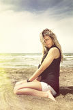 Young blonde girl relaxing on the beach sand. Wind in her blonde hair Royalty Free Stock Photos