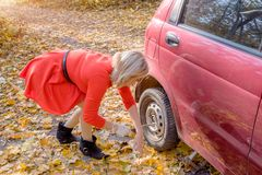 Young blonde girl replace car wheel on the roadside royalty free stock image