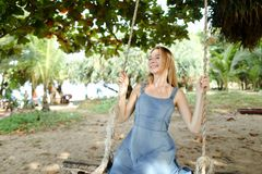 Young blonde girl riding on swing and wearing jeans sundress, sand in background. stock photos
