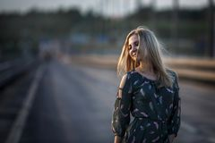 Young blonde girl on the road in the evening soft light of the sun. stock photo